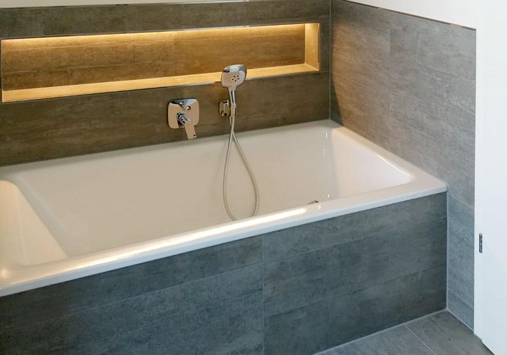 Badewanne mit Lichtlaufband und Steinfliesen
